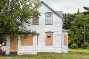 A white house, boarded up and condemned.